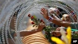 Seorang demonstran anti-pemerintah memberikan mawar pada tentara Thailand di gedung Kementerian Pertahanan di Bangkok pada demonstrasi Kamis (28/11).