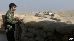 A militiaman of the Kurdistan Freedom Party, an Iranian Kurdish opposition group, looks over the sandbags at a section of the frontline near the Iraqi city of Kirkuk, Sept. 5, 2016.