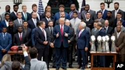 President Donald Trump stands with New England Patriots coach Bill Belichick, left, owner Robert Kraft, right, and team members during a ceremony on the South Lawn of the White House in Washington, April 19, 2017. Trump honored the team for their Super Bowl LI victory.