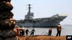 Indian navy's first aircraft carrier the INS Vikrant is drawn closer to shore at Darukhana ship breaking yard in Mumbai, India, Saturday, May 31, 2014.
