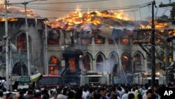 Kashmiri residents watch as firefighters try to extinguish a fire at the nearly 200-years-old Sheikh Abdul Qadir Jeelani Shrine, popularly known as Ghaus-e-Azam, or Dastgeer Sahab, in downtown Srinagar, India, June 25, 2012.