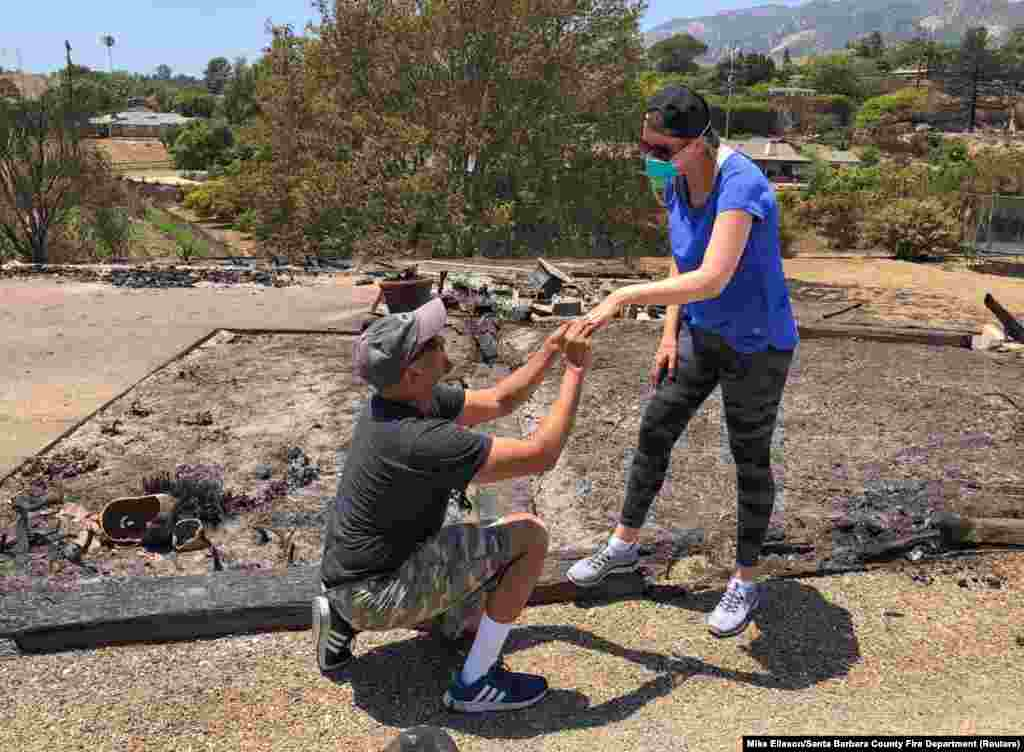 Ishu and Laura Rao, return to the rubble of their home which they lost in a wildfire, to retrieve their wedding ring, in Alameda, California, in this July 8, 2018 photo obtained from social media.
