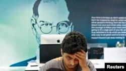 Seorang pegawai di India bekerja di ruangan dengan latar belakang gambar mendiang Steve Jobs di Start-up Village di Kinfra High Tech Park, Kochi. (Foto: Dok)