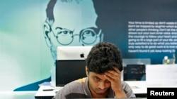 Un empleado trabaja con el fondo de un cartel del fundador de Apple, Steve Jobs, en la ciudad sureña de Kochi, en la India.