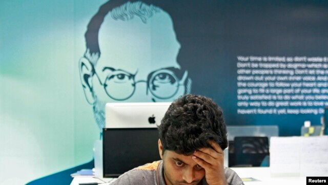 FILE - An image of Steve Jobs looks over the shoulder of computer workers in Kochi, India