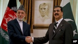 Afghan President Hamid Karzai, left, shakes hand with Pakistani Prime Minister Yousuf Raza Gilani prior to their meeting in Islamabad, Pakistan on Saturday, June 11, 2011