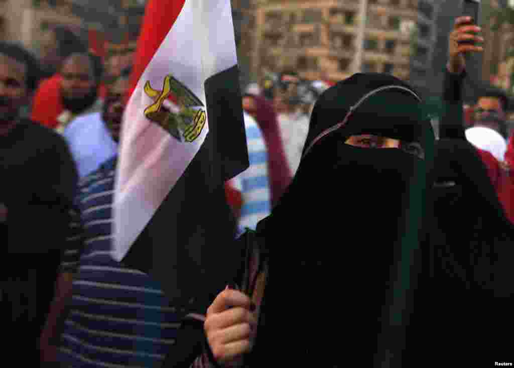 A supporter of Egypt's President Mohamed Morsi holds an Egyptian flag as as she and other protesters gather at Tahrir square, Cairo, Egypt, July 10, 2012.
