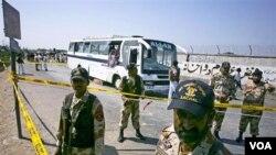 Tentara Pakistan berdiri di sekitar lokasi ledakan bom dekat dua bus di Karachi, Selasa (26/4).