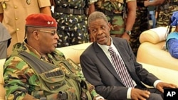 Guinea's acting president General Sekouba Konate, left, speaks with Prime Minister of the transitional government Jean Marie Dore during the inauguration ceremony of Camp Boiro in Conakry, 26 Jun 2010