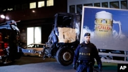 FILE - A destroyed truck is pulled away after it was driven into a department store in Stockholm, Sweden, April 8, 2017.