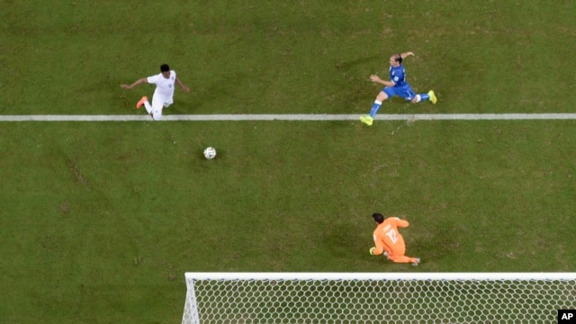 England's Daniel Sturridge, left, scores his team's first goal as Italy goalkeeper Salvatore Sirigu challenges, Arena da Amazonia in Manaus, Brazil, June 14, 2014.