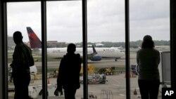 Tư liệu - Hành khách nhìn theo chiếc máy bay của hãng Delta Airline tiến vào Sân bay Quốc tế Atlanta Hartsfield-Jackson, ngày 14 tháng 4, 2015.
