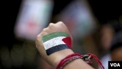 Salah seorang peserta pawai di Ramallah mengepalkan tangan yang bergambar bendera Palestina (8/9).