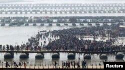 """Umat Hindu menyeberangi sungai Gangga di jembatan ponton setelah mandi di perairan di Sangam - pertemuan Sungai Gangga, Yamuna dan sungai Saraswati dalam rangkaian festival """"Kumbh Mela"""" di kota Allahabad, India utara, 10 Februari 2013. (REUTERS / Jitendra Prakash)."""