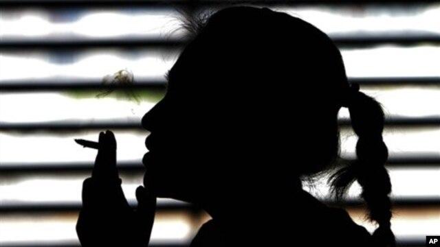A woman smokes a cigarette.