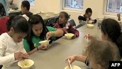 """Učenici koji učestvuju u programu """"Kafe za decu"""" uče o hranljivim sastojcima avokada dok prave namaz od avokada i pasulja"""