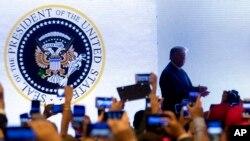 En esta fotografía del 23 de julio de 2019, el presidente Donald Trump sube al estrado en una cumbre juvenil del grupo conservador Turning Point USA en Washington. Sobre el fondo se ve un sello presidencial en el que el águila está agarrando palos de golf en lugar de flechas.