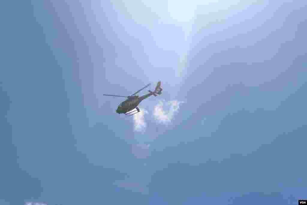 在天空盘旋的警察直升机,用高音喇叭呼叫人群离去