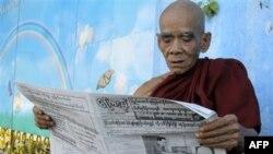 Một tu sĩ đọc báo bên ngoài bệnh viện miễn phí Jivita Dhana dành cho các nhà sư ở Miến Ðiện