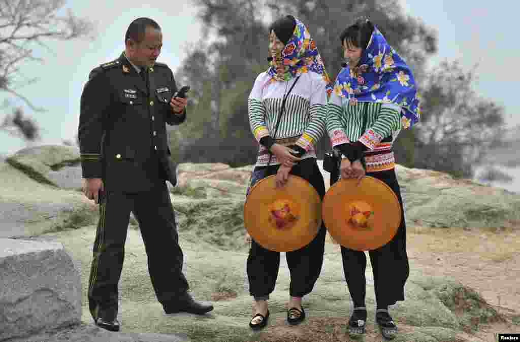A People's Liberation Army officer looks at his mobile phone as he speaks with two Hui'an maiden tourist guides in Hui'an county, Fujian province, China, Dec. 8, 2013.