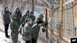 FILE - South Korean President Park Geun-hye, second right, looks at the North Korean side through a barbed wire fence during a 2013 trip to the Demilitarized Zone in Yanggu, South Korea.