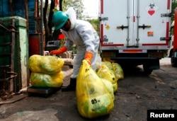 Petugas perusahaan insinerator mengenakan alat pelindung diri tengah mengumpulkan kantong berisi sampah medis (dok: REUTERS/Ajeng Dinar Ulfiana)