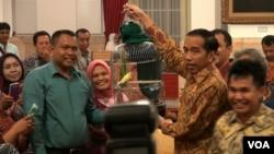 Presiden Joko Widodo menerima hadiah burung dari pedagang pasar burung, di Istana Negara, Jakarta (3/9). (VOA/Ahadian Utama)