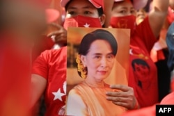 A Myanmar migrant holds up an image of Aung San Suu Kyi during a demonstration outside the Myanmar embassy in Bangkok on February 1, 2021, after Myanmar's military detained the country's de facto leader Suu Kyi and the country's president in a coup.