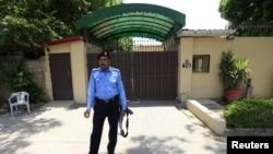 Seorang polisi berjaga-jaga di luar kantor Save the Children di Islamabad, Pakistan, 12 Juni 2015.