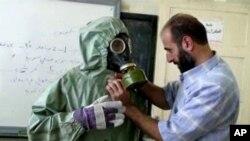 Foto Archivo - 18 de septiembre de 2013 muestra un voluntario ajustando a la máscara de gas de los estudiantes y traje de protección durante una sesión sobre reaccionar a un ataque de armas químicas, en Alepo, Siria.