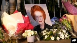 "Sebuah potret mendiang ""Iron Lady"" Margaret Thatcer dan karangan bunga dari masyarakat yang berduka menghiasi pagar rumah kediaman almarhumah di Belgravia, London (8/4)."