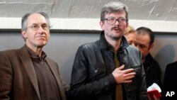 FILE - The new chief editor of French satirical magazine Charlie Hebdo, Gerard Biard, left, and Cartoonist Renald Luzier, known as Luz leave after a press conference in Paris, France.