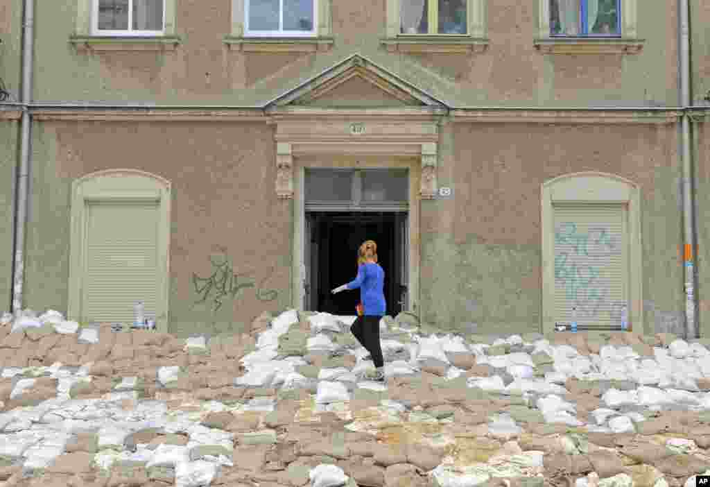 A woman stands on a wall of sandbags in front of a house in Dresden, eastern Germany. Heavy rainfalls cause flooding along rivers and lakes in Germany, Austria, Switzerland and the Czech Republic.