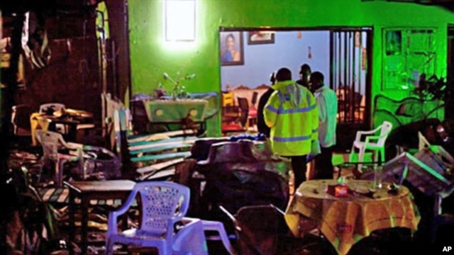 Ugandan police inspect the destroyed Ethiopian Village restaurant in Kampala after twin bomb blasts tore through crowds of football fans, killing 64 people, 11 Jul 2010