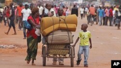 FILE - A family with their belongings on a makeshift trolley in the city of Bangui, Central African Republic, as clashes sectarian clashes erupted between rivaling Christian and Muslim militias, Sept. 30, 2015.