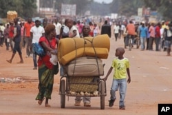 FILE - A family with there belongings on a makeshift trolley in the city of Bangui, Central African Republic, as clashes sectarian clashes erupted between rivaling Christian and Muslim militias, Sept. 30, 2015.