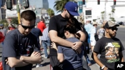 Reed Broschart, center, hugs his girlfriend Aria James on the Las Vegas Strip in the aftermath of a mass shooting at a concert in Las Vegas, Oct. 2, 2017.