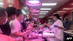 People buy items at a supermarket in Wuhan, China, August 2, 2021, as authorities said they would test its entire population for Covid-19 after the central Chinese city where the coronavirus emerged reported its first local infections in more than a year.