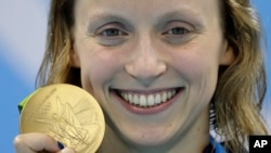 United States' Katie Ledecky shows off her gold medal in the women's 800-meter freestyle medals ceremony during the swimming competitions at the 2016 Summer Olympics, in Rio de Janeiro, Brazil, Aug. 12, 2016.