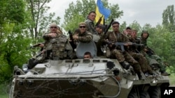 Ukrainian soldiers sit on top of an APC after a Ukrainian check was attacked by pro-Russians near the village of Blahodatne, eastern Ukraine, May 22, 2014.