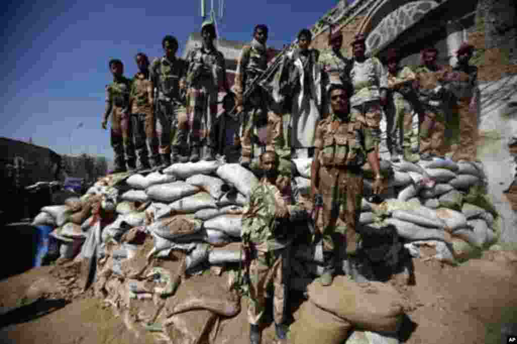 Defected army soldiers backing anti-government protesters stand guard on sandbags as protesters march to demand the release of detained fellow protesters in Sanaa January 26, 2012. REUTERS/Khaled Abdullah (YEMEN - Tags: POLITICS CIVIL UNREST MILITARY)