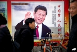 FILE - People walk past a propaganda billboard showing Chinese President Xi Jinping on a street in Beijing, China, March 2, 2018.