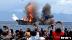 Warga mengambil gambar kapal ikan yang terbakar setelah pemerintah menghancurkan kapal-kapal asing yang tertangkap mencuri ikan di wilayah perairan Indonesia, di Desa Morela, P Ambon, 1 April 2017. (Antara Foto)