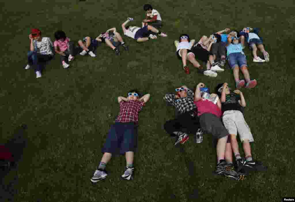 School children using solar viewers lie down on a lawn as they observe an annular eclipse at Hirai Daini Elementary School, Tokyo, Japan, May 21, 2012. Un grupo de estudiantes Hirai Daini, escuela primaria de Tokio, Japón, utilizan protectores para
