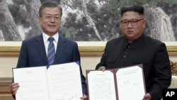 In this image made from video provided by Korea Broadcasting System (KBS), S. Korean President Moon Jae-in, left, and N. Korean leader Kim Jong Un pose after signing documents in Pyongyang, North Korea, Sept. 19, 2018.