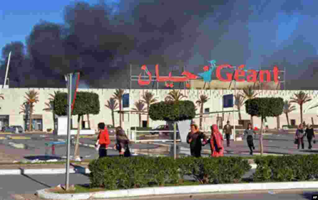 A supermarket is on fire after it was sacked and looted in Bizerte, Tunisia, 15 Jan 2011.