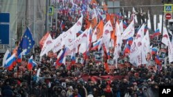 Orang-orang membawa bendera berbagai gerakan, berpawai untuk memperingati tiga tahun pembunuhan pemimpin oposisi Boris Nemtsov di Moskow, Rusia, Minggu, 25 Februari 2018.