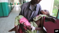 An man carries his malnourished child through the corridors inside Banadir hospital in Somalia's capital, Mogadishu, Aug. 9, 2011. (Reuters)
