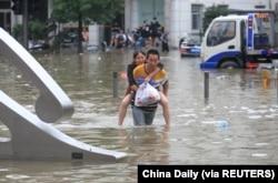 河南省鄭州市一名男子背著一名女子趟過滿是洪水的街道。 (2021年7月21日)
