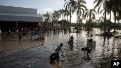 18일 아카플코 남부에서 시민들이 허리까지 차오른 물사이를 지나고있다.